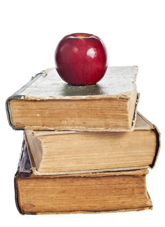 stack of books with an apple on a white background photo