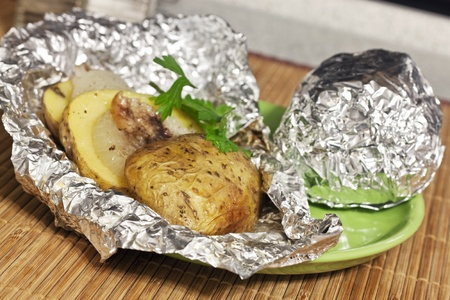 baked potatoes in foil on a plate photo