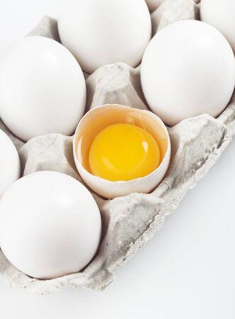 yolk: Yolk in a eggshell with white eggs in a carton