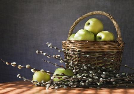 Still. The morning sun lights up a basket of apples photo
