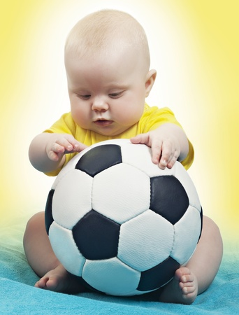 child in a yellow-blue background, with a soccer ball Stock Photo - 13208978