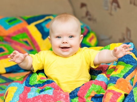 six months: smiling child stretches his hands to the camera Stock Photo