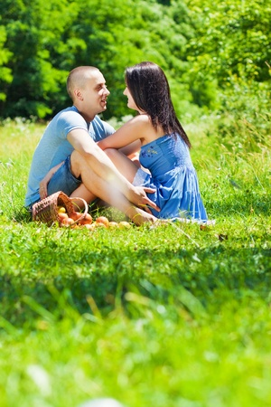 young couple sitting on the grass in the park photo
