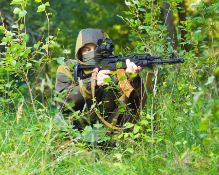 soldier in camouflage with a Kalashnikov assault rifle, shooting in the woods photo