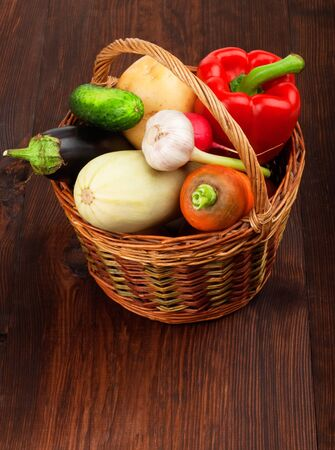 Fresh ripe vegetables in a basket on wooden table photo