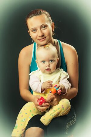 beautiful caucasian good mum holding her daughter in her arms on a dark background  Stock Photo - 15719755