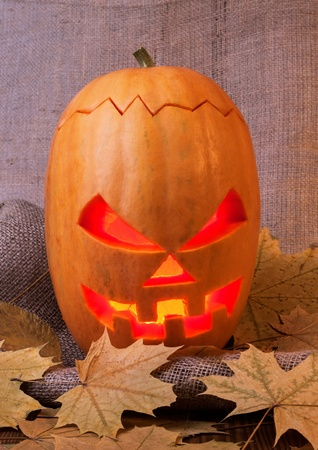 Halloween pumpkin on burlap background with leaves lying on wooden boards photo