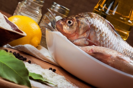 Fresh carp on a kitchen table with lemon and flour photo