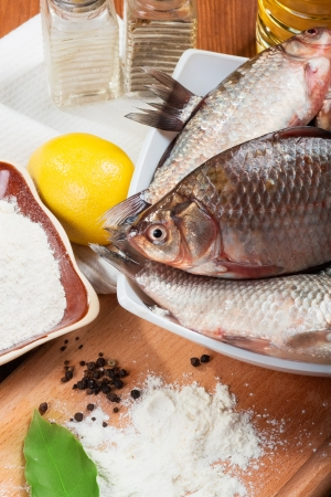 Fresh carp on a kitchen table with lemon and flour Stock Photo - 15957302