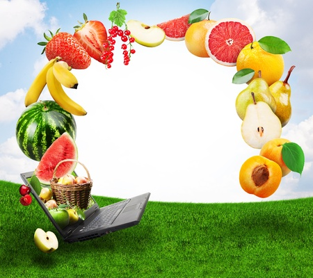 Collage of fresh fruits emerging from laptop photo