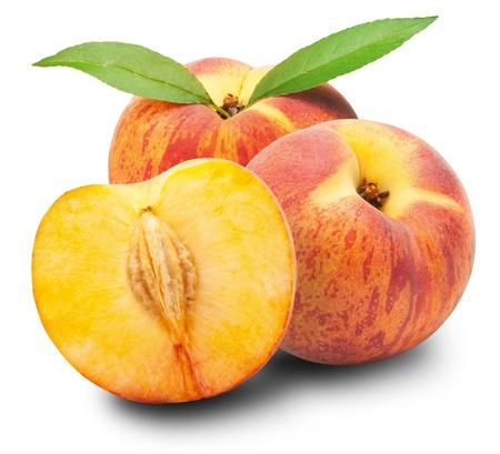Rijpe perzik vruchten met bladeren en slises op witte achtergrond Stockfoto