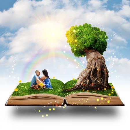 若いカップルの愛の魔法の木のそばの芝生の上に座って。