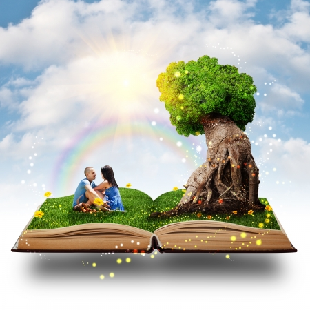 magic book: Young couple sitting on the grass near the magic tree of love.
