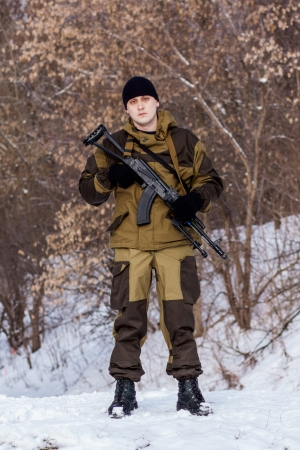 Russian soldier in winter uniform with the machine gun on the forest background photo