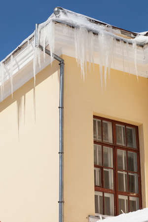 rust covered: icicles hang from rain gutters on a chilly winter day  Stock Photo