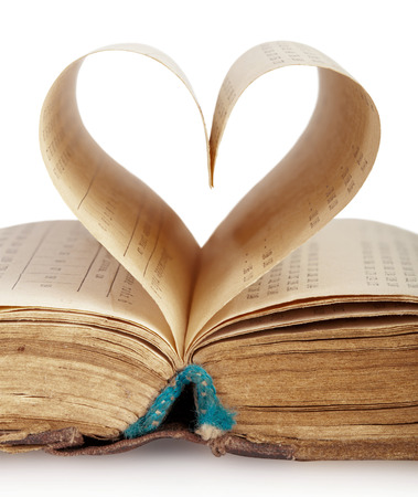 Book with opened pages of shape of heart isolated on white background  photo