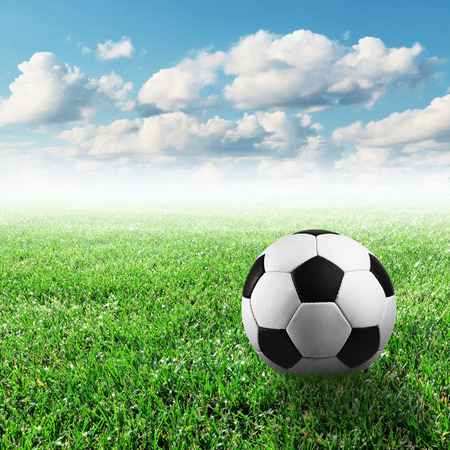 soccer ball on the green grass with the bright sky photo