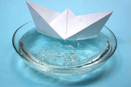 Paper ship in a bowl with water photo