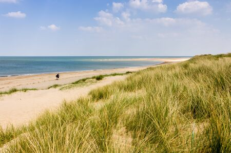 Two people with rucksacks walking down a sandy beach on a sunny day in Norfolk, UK Stock Photo