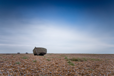A solitary fishing boat on a shingle beach against a cloudy sky