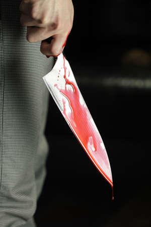 holding a knife: Man holding bloody knife