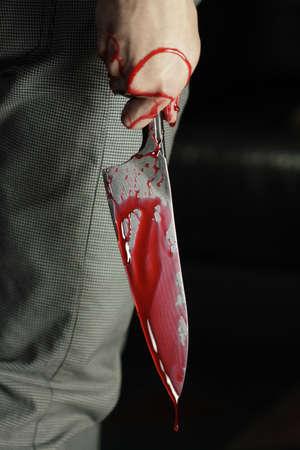 tremante: Uomo che tiene un coltello sanguinante Archivio Fotografico