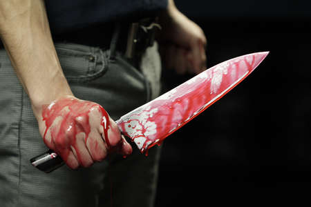 blade cut: Man holding bloody knife