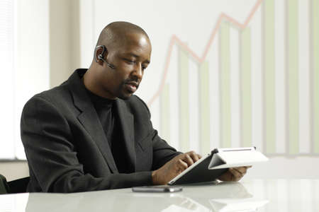 African American business man on his blue tooth using tablet
