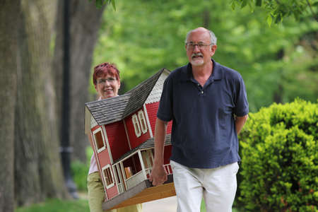 Older couple carrying a suburban home in residential neighborhood, horizontal photo