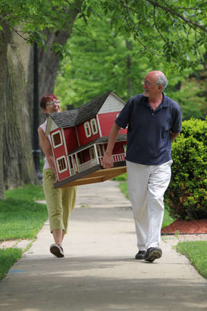 housing development: Older couple carrying a suburban home in residential neighborhood, vertical