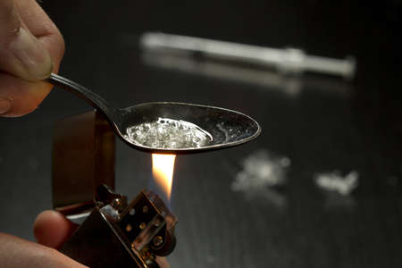 drug abuse: Man cooking heroin