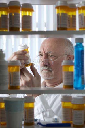 Senior man reading prescription medication Stock Photo - 21032300