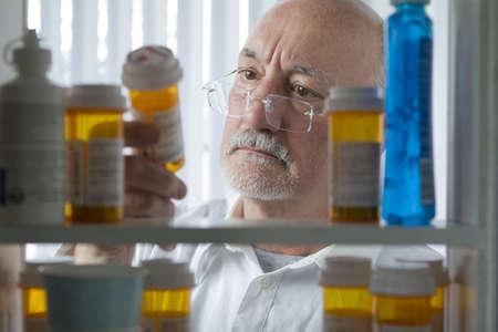Senior man reading prescription bottle