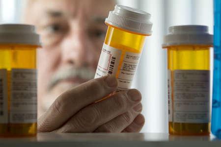 medecine: Senior homme lisant l'étiquette de prescription Banque d'images
