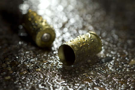 crime: Two bullet casings on a rainy day Stock Photo