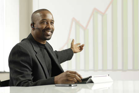 African American business man presenting profits, horizontal Фото со стока