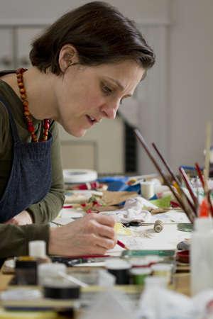 artist painting: Female artist in her studio working on her art, vertical Stock Photo