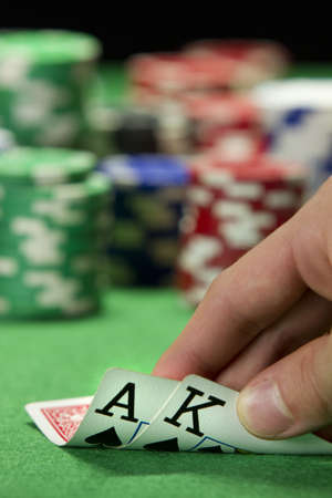 card player: Card player checks his hand, vertical