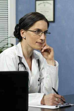 Female doctor listening to patient and taking notes, vertical photo