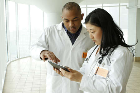 Female Asian doctor with African American doctor looking over charts on tablet, horizontal Stock Photo