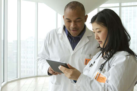 Female Asian doctor with African American doctor looking over charts on tablet, horizontal
