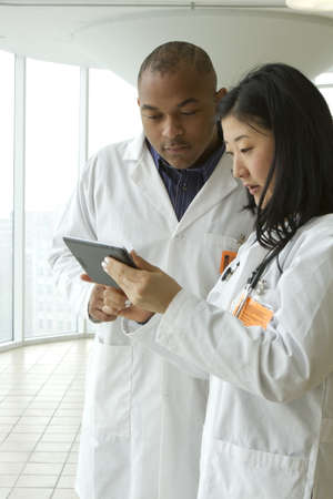 Female Asian doctor with African American doctor looking over charts on tablet, vertical