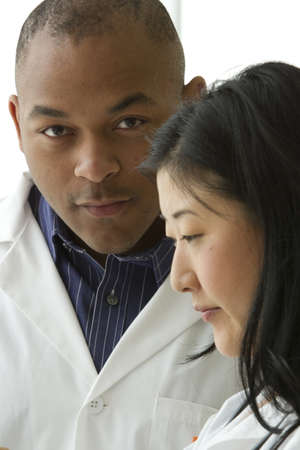 Female Asian doctor with African American doctor, vertical