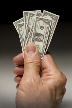 Man holding tiny dollar bills, vertical Stock Photo - 21096230