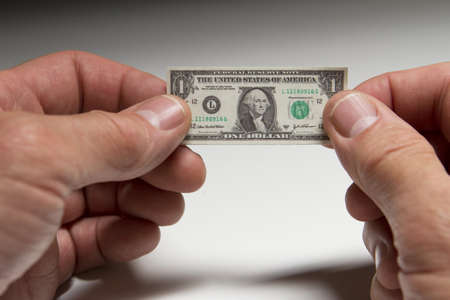 Hands holding tiny dollar bill, horizontal Stock Photo - 21096234