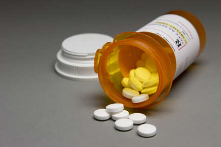 Pills flowing out of a prescription bottle, horizontal