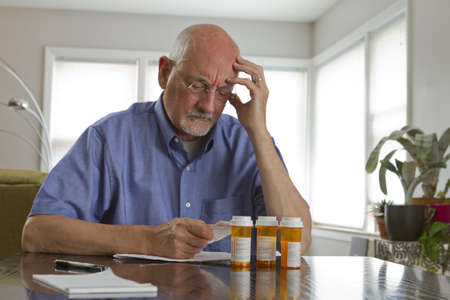 pills bottle: Older man with prescription medications, horizontal