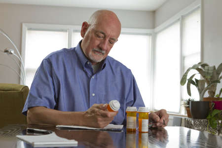 Older man with prescription medications, horizontal photo