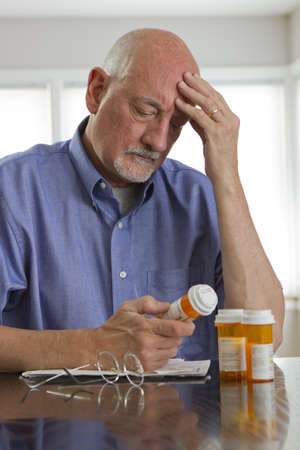 Older man with prescription medications, vertical  photo