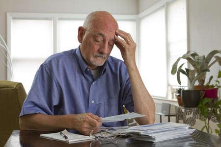 expensive: Older man paying bills - horizontal